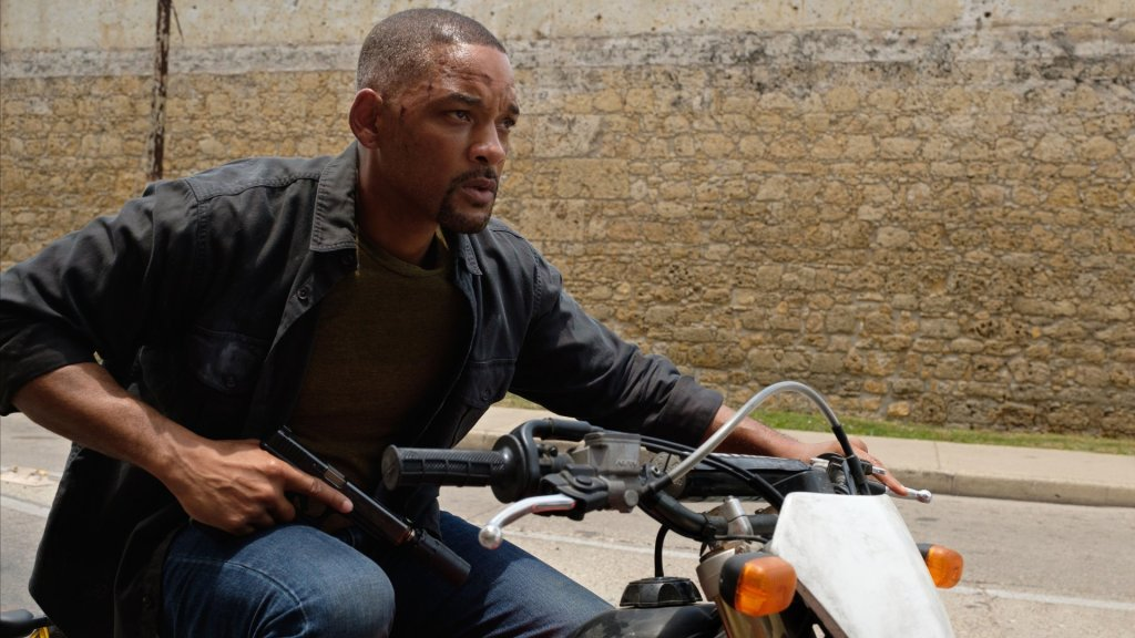 Henry (Will Smith) on a motorcycle holidng a gun.