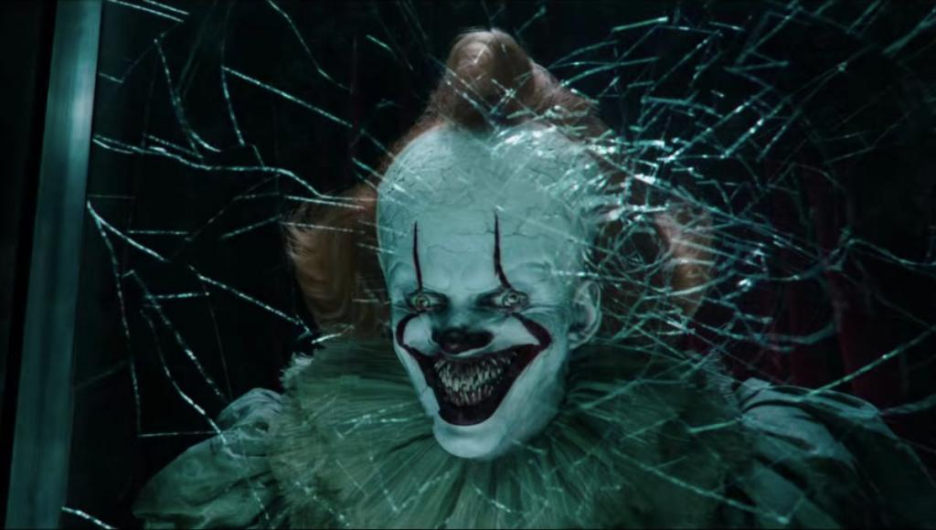 Pennywise (Bill Skarsgård) smiling behind a fractured glass wall, showing a mouth full of sharp teeth.