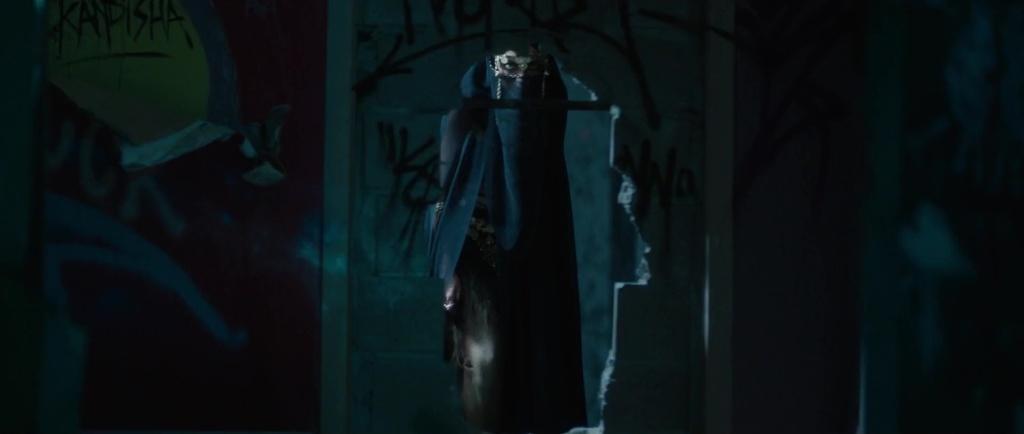 Kandisha (Mériem Sarolie) - a veiled woman - seen through a hole in the wall.