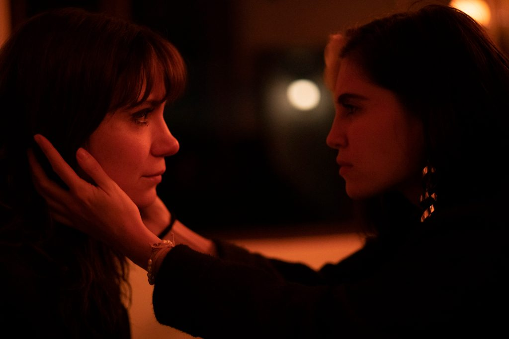 Ana María (Ana María Cuellar) cradling Diana's (Diana Wiswell) face.