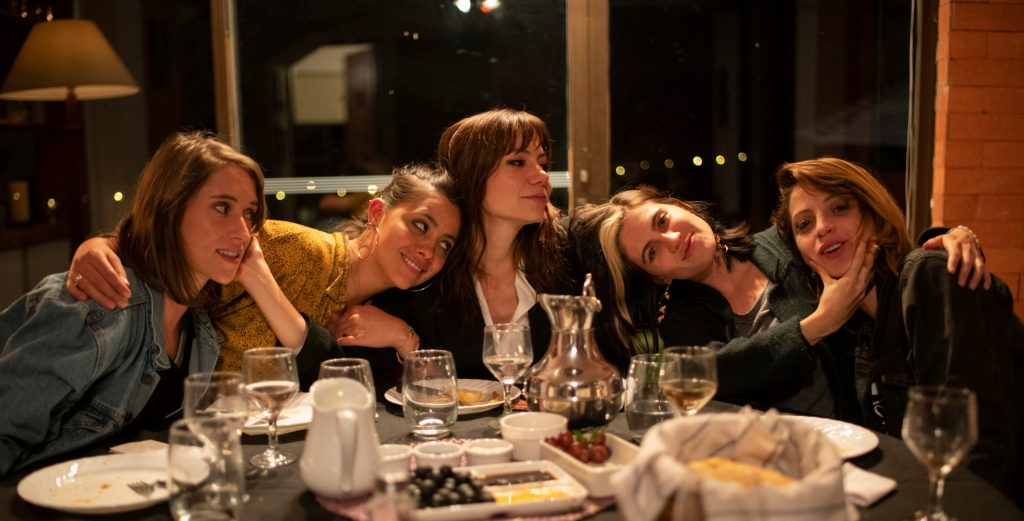 The five women around the dinner table, cuddled together.