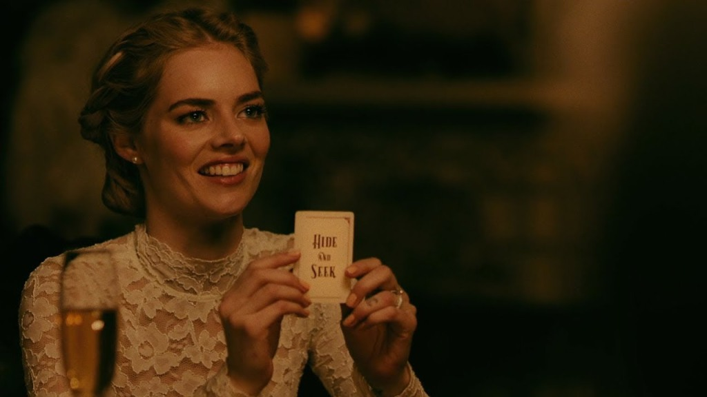 """Grace (Samara Weaving) holding up a card that says """"Hide and Seek""""."""
