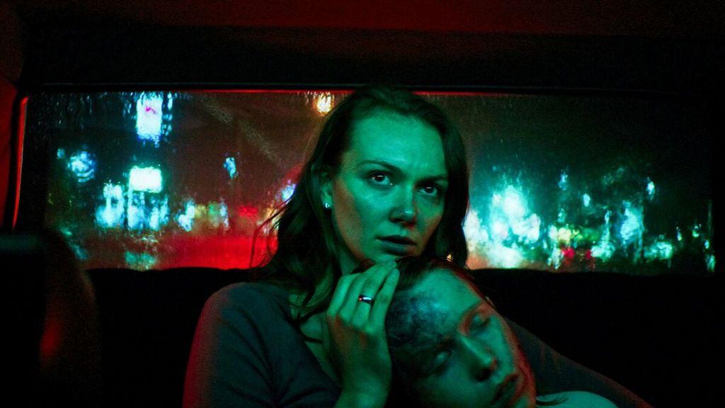Laura (Andi Matichak) cradling her son David (Luke David Blumm) in a taxi. He looks sick and bruised.