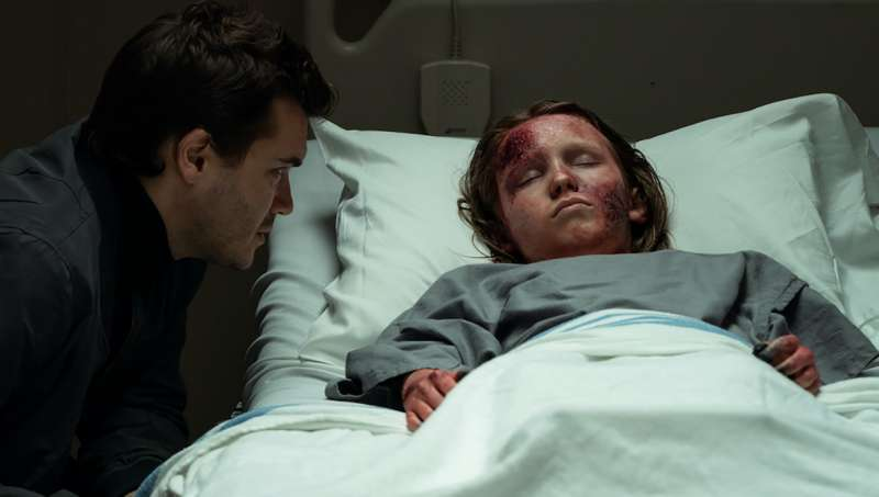 Police officer Paul (Emile Hirsch) sitting at David's (Luke David Blumm) bed in the hospital.