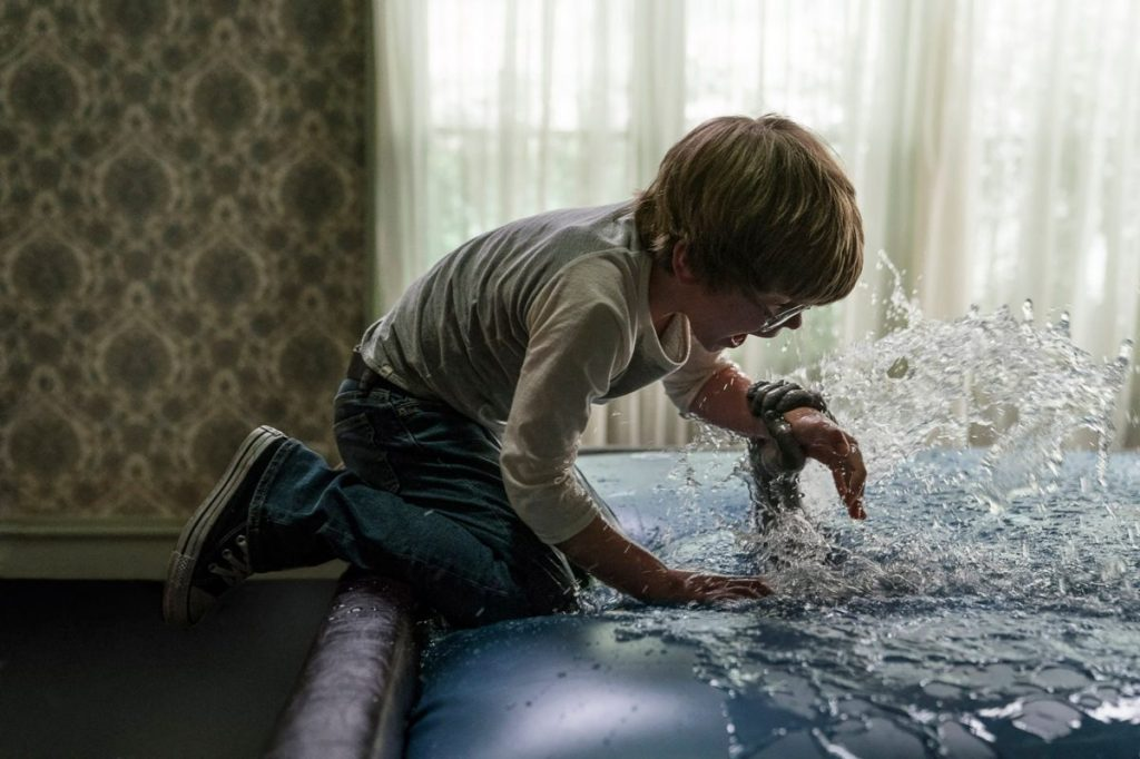 David (Julian Hilliard) being grabbed by a hand emerging from a waterbed.