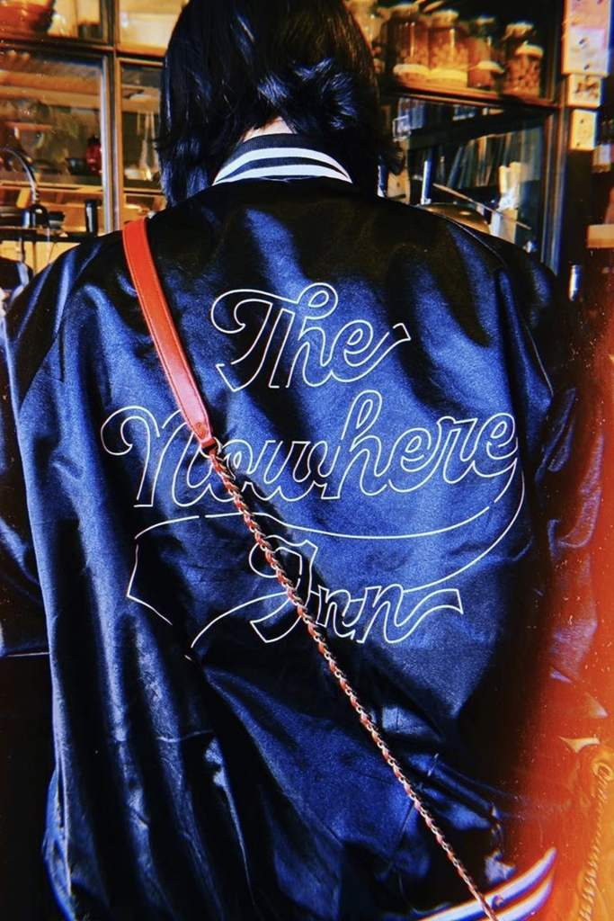 The film poster showing a woman (possibly St Vincent) from behind, wearing a jacket that says The Nowhere Inn on the back.