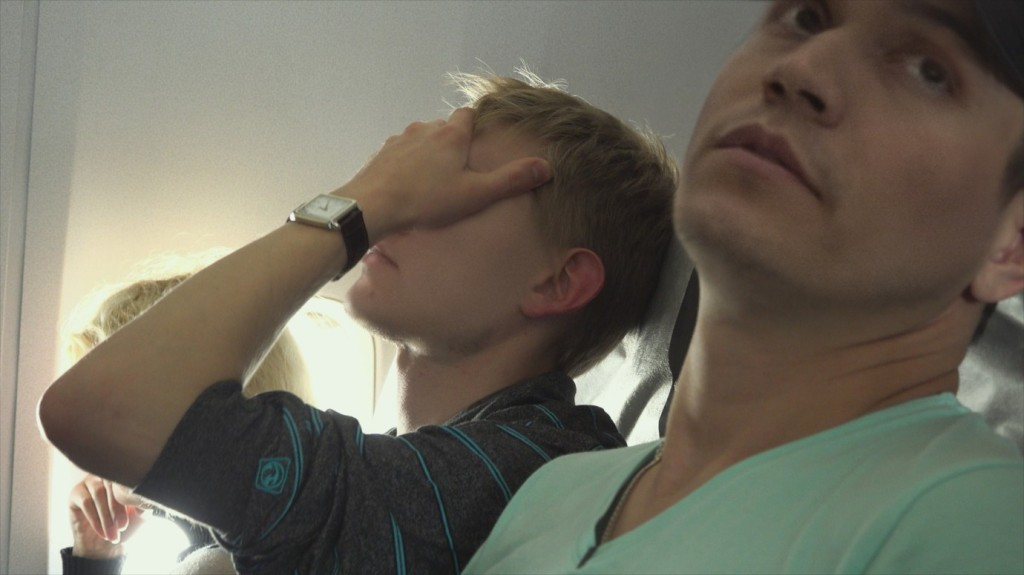 Maxim Lapunov (in his fake face) and his boyfriend on a plane. Both are looking tired and worried.