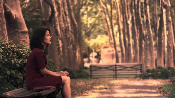 Gewn (Jacqueline Kim) sitting thoughtfully in a park.