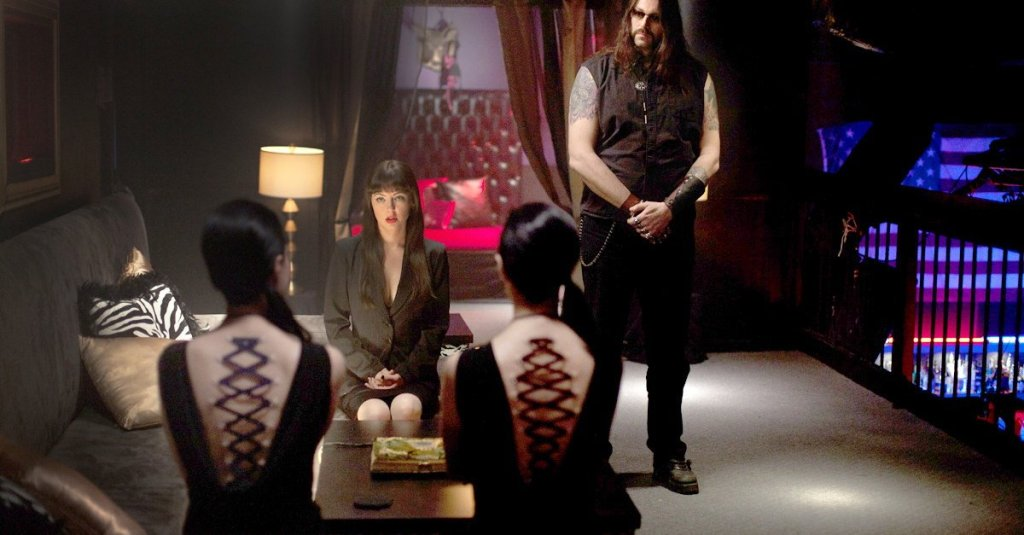 Mary (Katharine Isabelle) meeting with prospective clients. We can only see their backs that have rope threaded directly through the skin as if it was a corset.