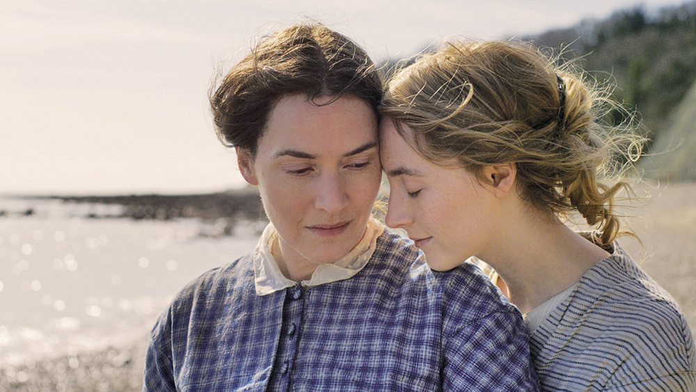 Mary (Kate Winslet) and Charlotte (Saoirse Ronan) cuddling on the beach.