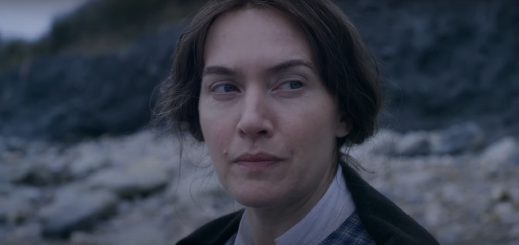Mary (Kate Winslet) on the beach, looking critical.