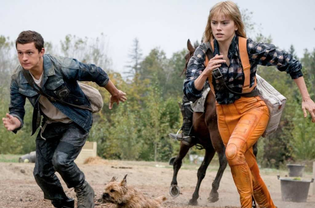 Todd (Tom Holland), Viola (Daisy Ridley) and Manchee running from a horse and its rider.