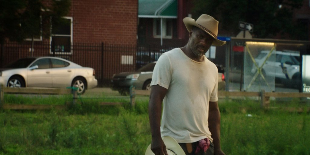 Harp (Idris Elba) on a meadow just outside of an apartment building and a city street.