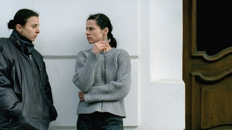 Ariane (Anna Bolk) and Isabel (Angela Schanelec) leaning against a building together.