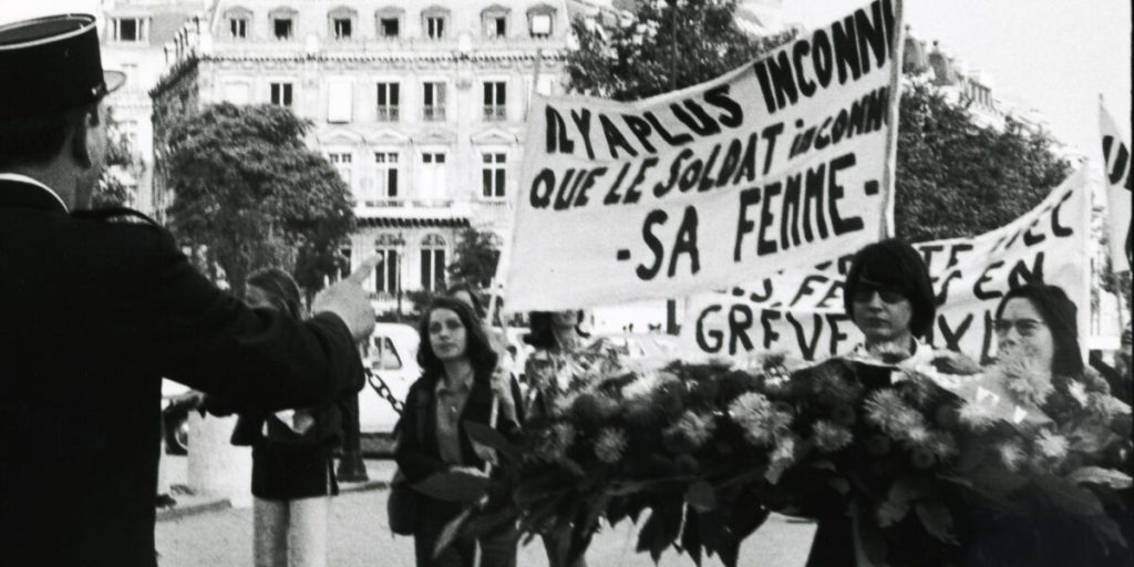 """Image of a feminist protest, women are carrying a sign that says """"There is someone more unknown than the unknown soldier - his wife"""" in French."""
