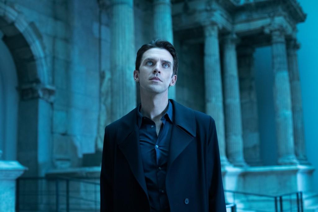 Tom (Dan Stevens) standing in a historical museum, looking at ruins.