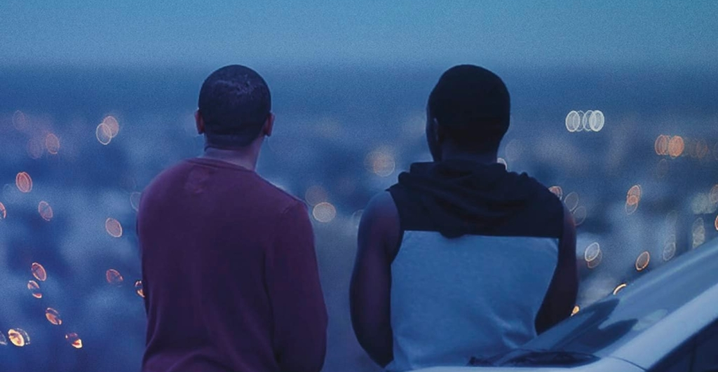 George (Adriano Visagie) and Simeon (Simon Hanga) looking over the city at night.