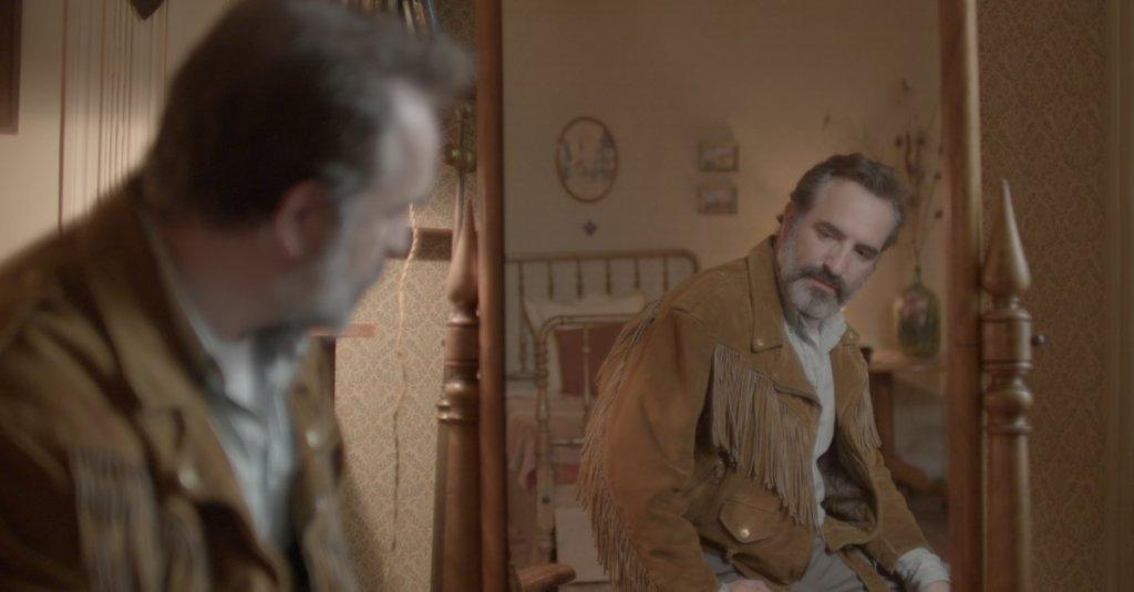 Georges (Jean Dujardin) admiring himself in his deerskin jacket in the mirror.