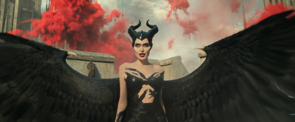 Maleficent (Angelina Jolie) with her black wings spread wide, explosions in the sky behind her.