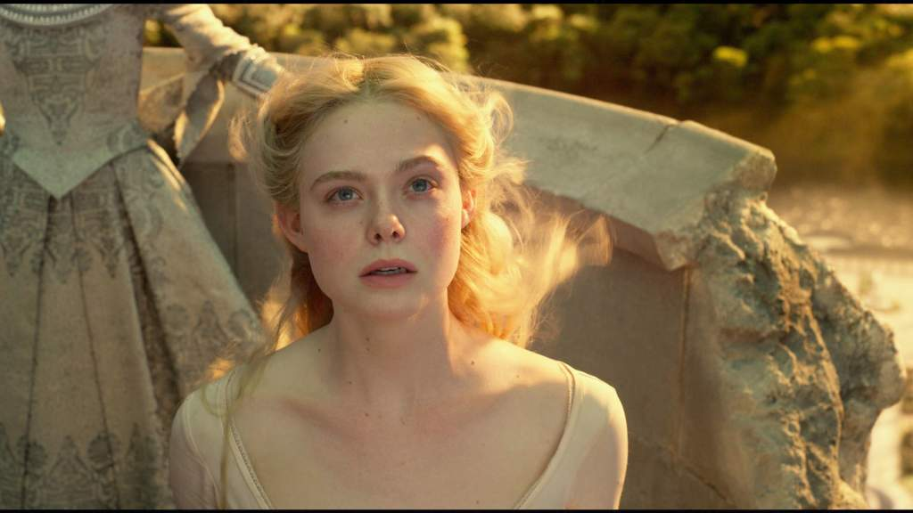 Aurora (Elle Fanning) looking up at the sky.