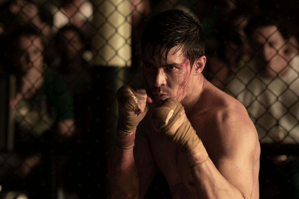 Cole Young (Lewis Tan) boxing in a cage fight.