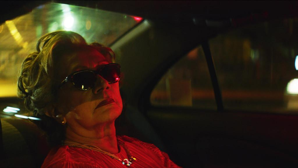 Nona (Josefina Ramírez) in the backseat of a car with her sunglasses on at night.