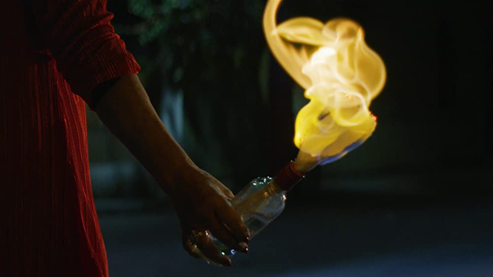 A hand holding a burning Molotov cocktail.
