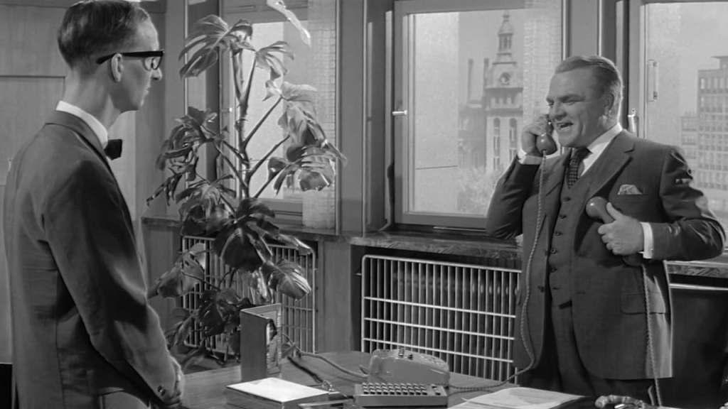 C.R. MacNamara (James Cagney) on the phone in his office.