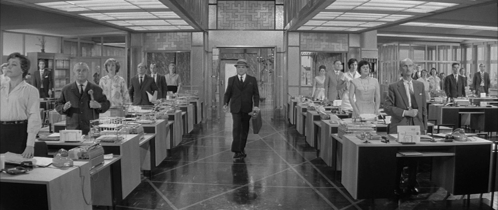 C.R. MacNamara (James Cagney) arriving in his office, with all employees standing at attention while he walks past.
