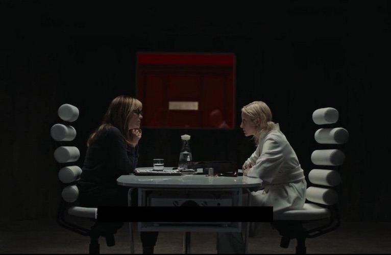 Girder (Jennifer Jason Leigh) checking in with Tasya (Andrea Riseborough) after her mission.