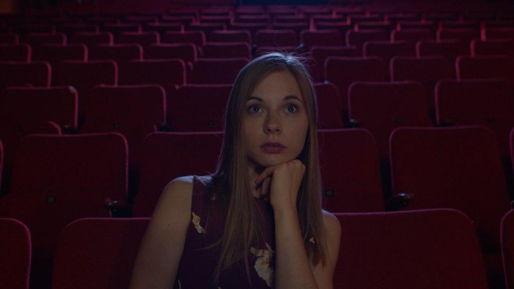 Claudia (Hannah Zieziula) in an otherwise empty cinema.