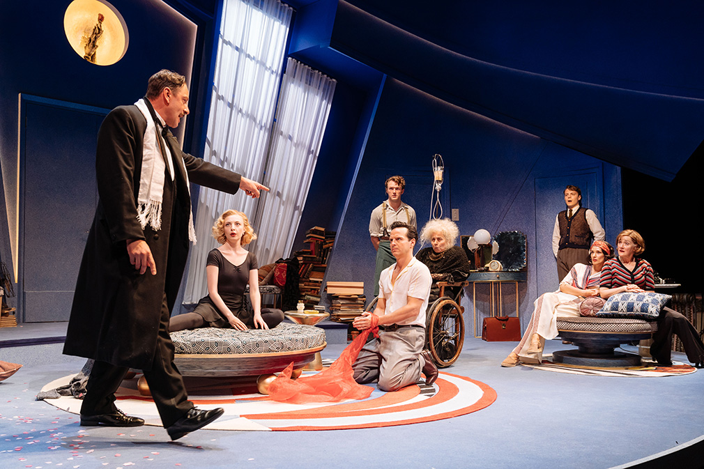 Almost the entire cast on stage in Garry's (Andrew Scott) apartment. Joe (Enzo Cilenti) is strutting angrily and points a finger at Garry.