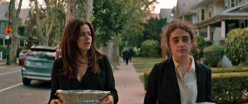 Maya (Molly Gordon) and Danielle (Rachel Sennott) carrying some food to the car.