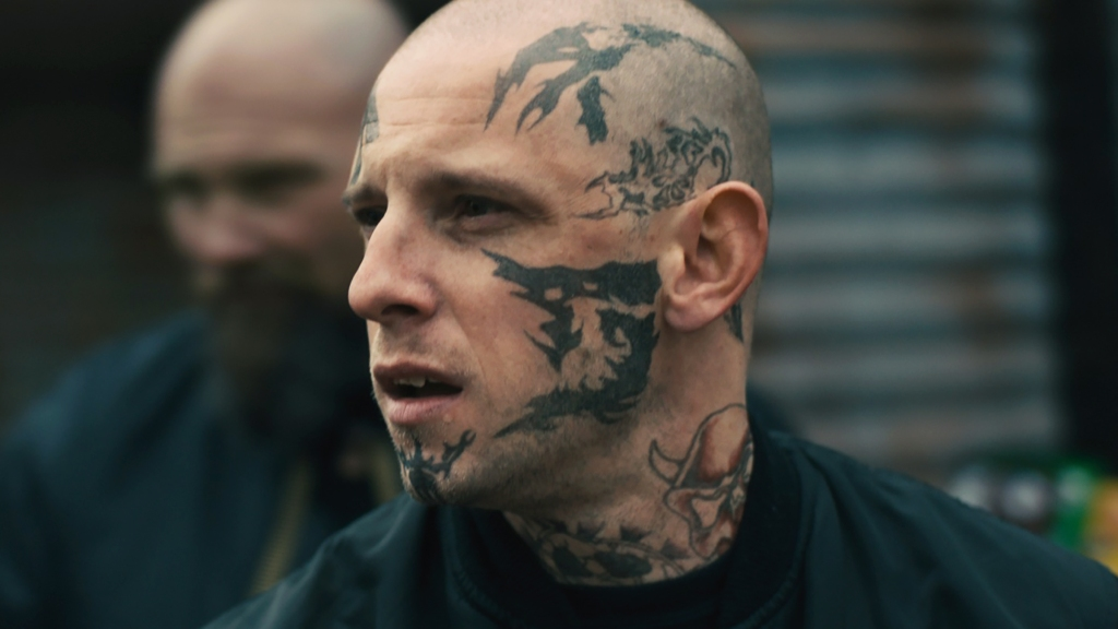 Bryon (Jamie Bell), his face full of tattoos.