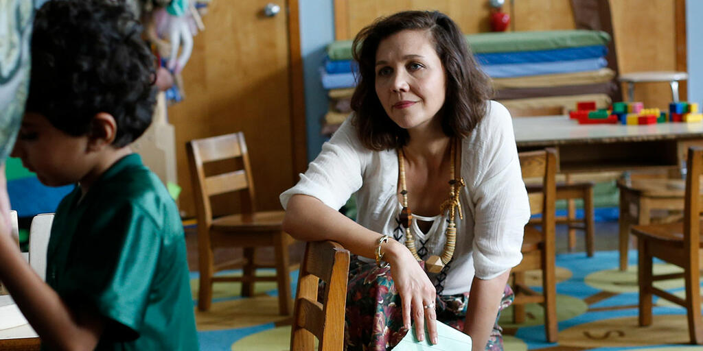 Lisa (Maggie Gyllenhaal) looking lovingly at Jimmy (Parker Sevak) who is turned away from her.
