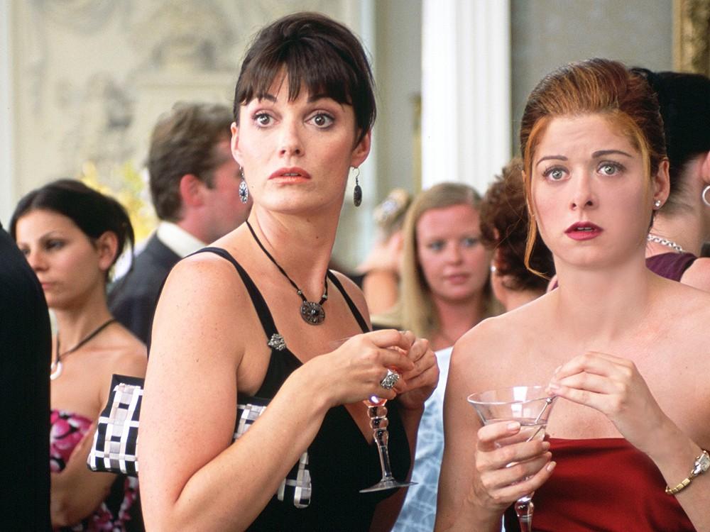 TJ (Sarah Parish) and Kat (Debra Messing) looking shocked.