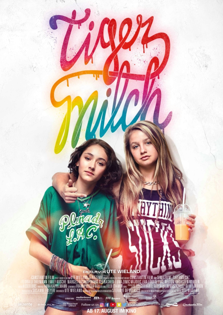 The film poster showing Jameelah (Emily Kusche) and Nini (Flora Thiemann) with their arms around each other. Nini is showing her middle finger.