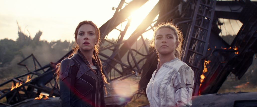Natasha (Scarlett Johansson) and Yelena (Florence Pugh) standing in front of some wreckage.