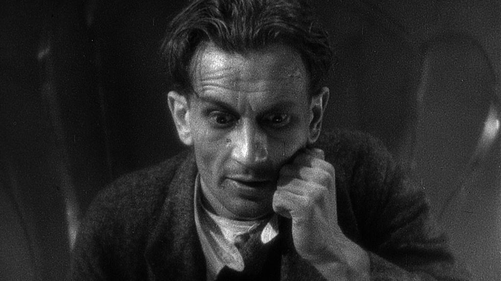 A distressed looking Hofmeister (Karl Meixner) pressing his fist against his cheek.