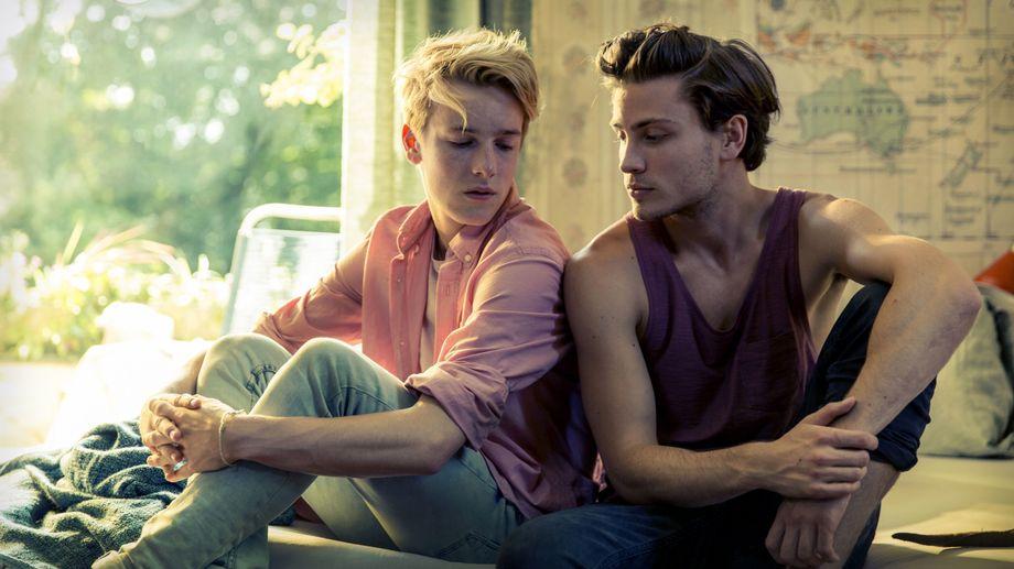 Phil (Louis Hofmann) and Nicholas (Jannik Schümann) sitting back to back in Phil's bed.