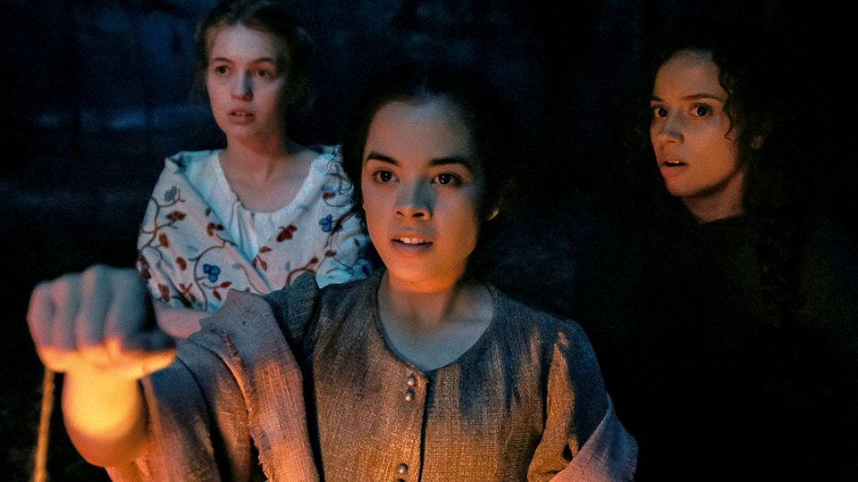 Lizzie (Julia Rehwald), Hannah (Olivia Scott Welch) and Deena as Sarah (Kiana Madeira) making their way through the dark forest with a lantern.