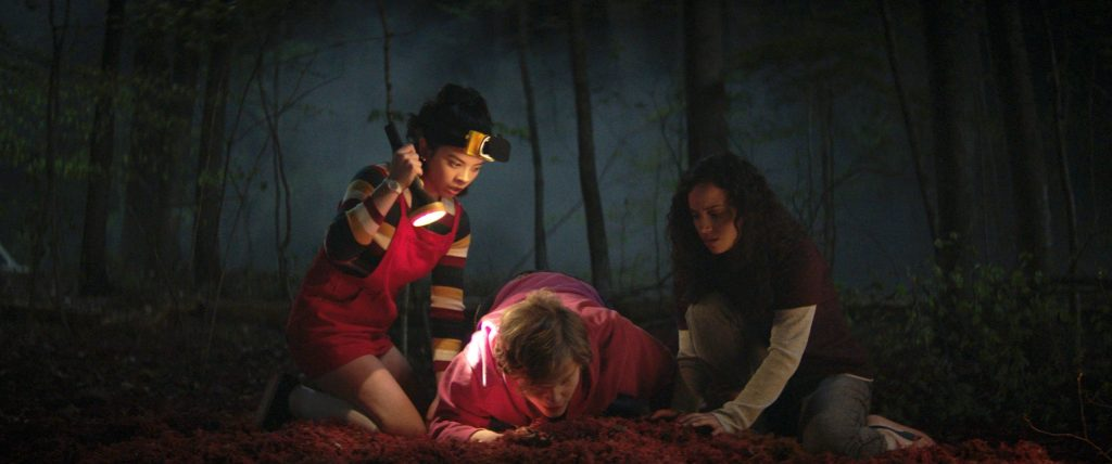 Kate (Julia Rehwald), Simon (Fred Hechinger) and Deena (Kiana Madeira) looking closely at something on the forest floor at night.