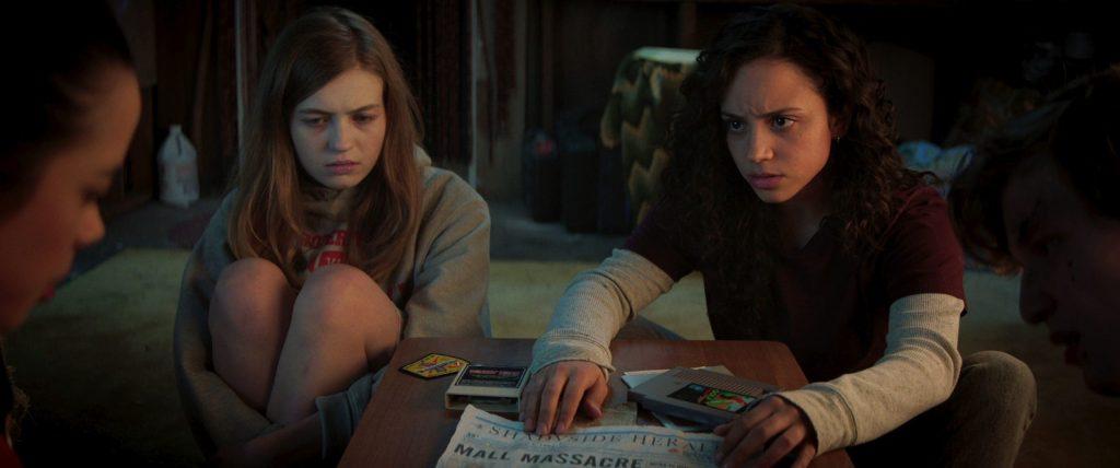 Sam (Olivia Scott Welch) and Deena (Kiana Madeira) shoving a newspaper article at Kate (Julia Rehwald).