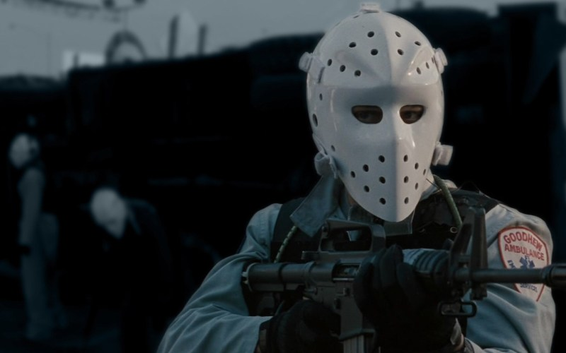 A masked man aiming an automated weapon.