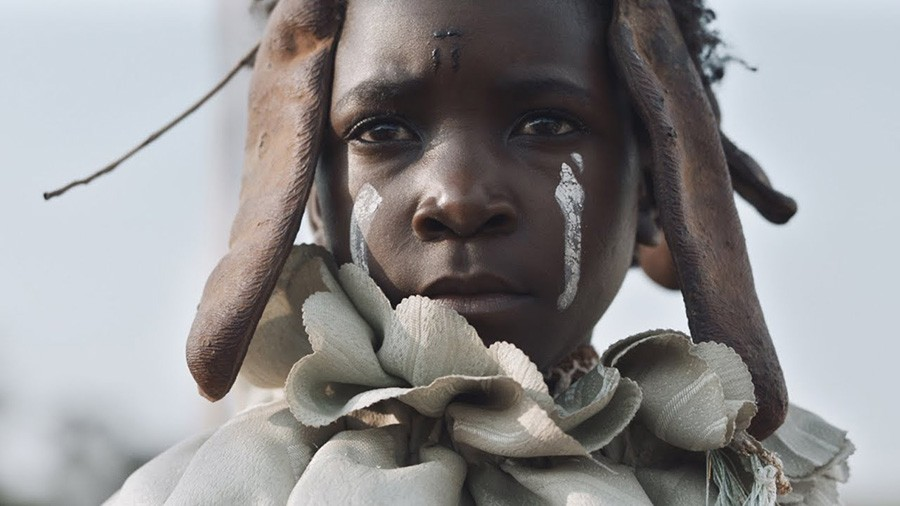 Shula (Maggie Mulubwa) in her witch dress, with white color on her cheeks.