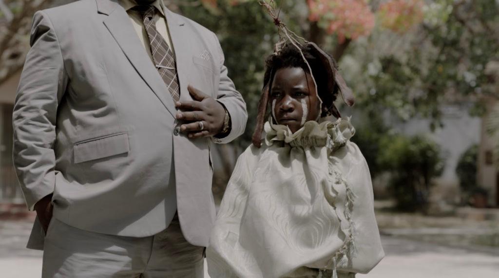 Shula (Maggie Mulubwa) standing next to Mr Banda (Henry B.J. Phiri).