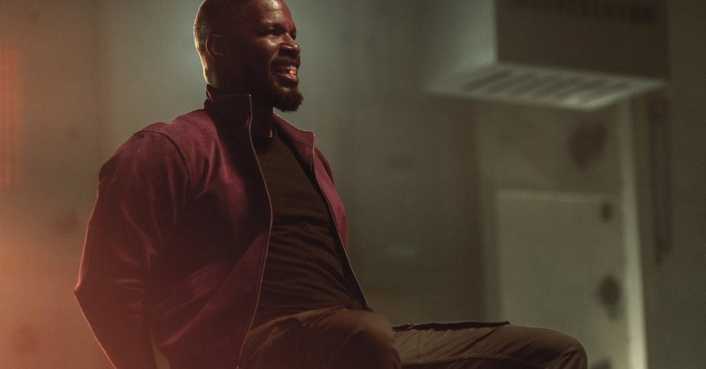 Art (Jamie Foxx) tied to a chair, a glowing pill between his teeth.
