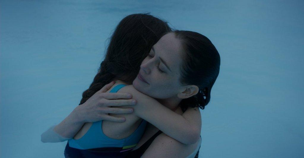 Sarah (Eva Green) cradling her daughter Stella (Zélie Boulant) in the pool.