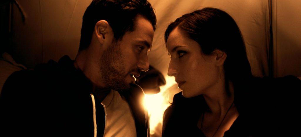 Casper (Sam Rosen) and Rebecca (Zoe Lister-Jones) almost kissing in a tent.