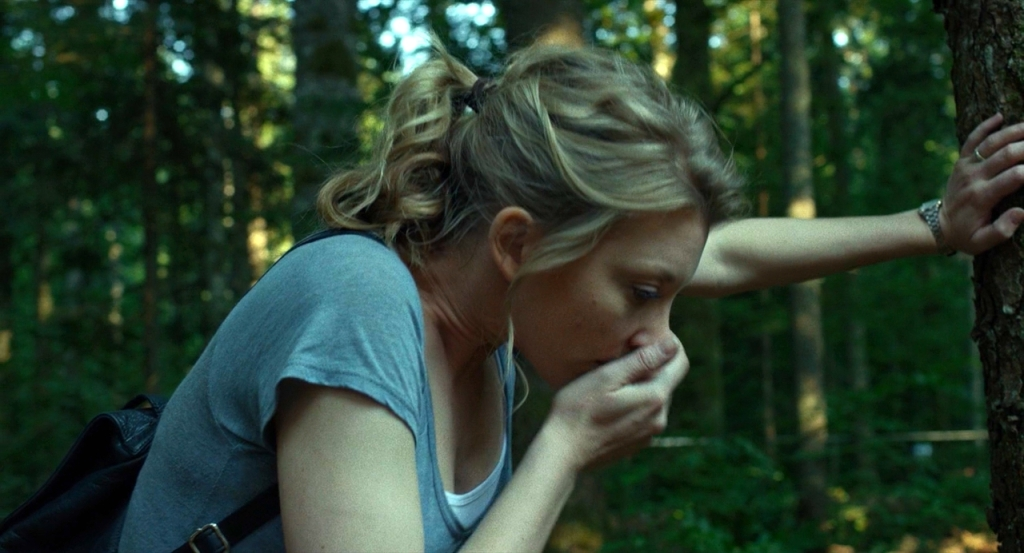 Sara (Natalie Dormer) leaning against a tree, one hand covering her face as if she's about to throw up.